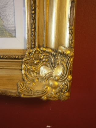 Gilt frame against rich red wall