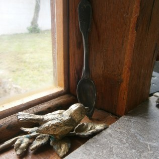 A little brass bird with a pewter spoon discovered in the old pig sty.